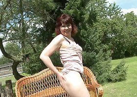 Pale skinned mature woman pleasuring herself outdoors